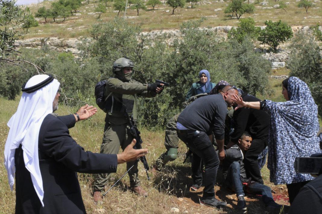 Ισραηλινός στρατιώτης δείχνει το πιστόλι του σε μια ομάδα Παλαιστινίων.